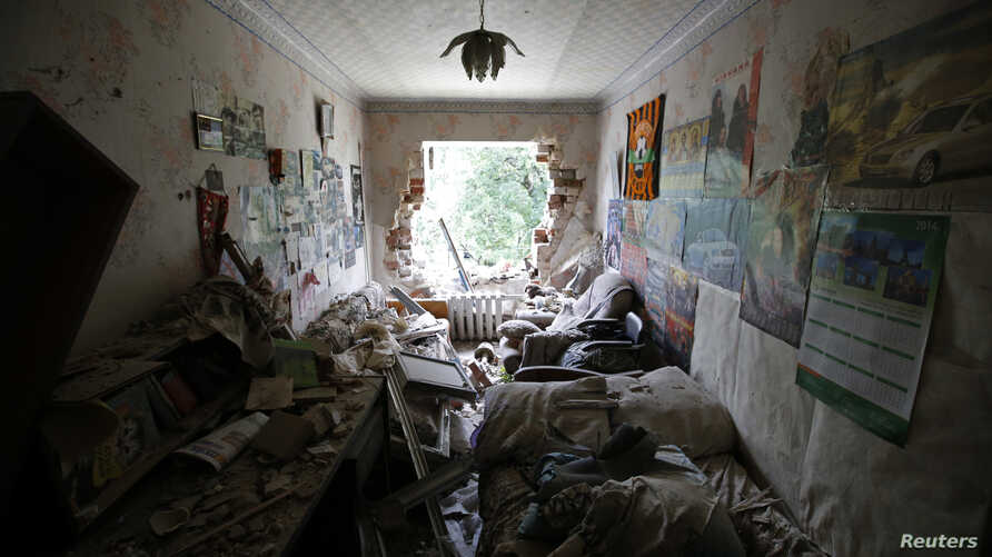 An interior view shows a damaged apartment building following what locals say was recent shelling by Ukrainian forces in the settlement of Maryinka outside Donetsk, July 12, 2014.