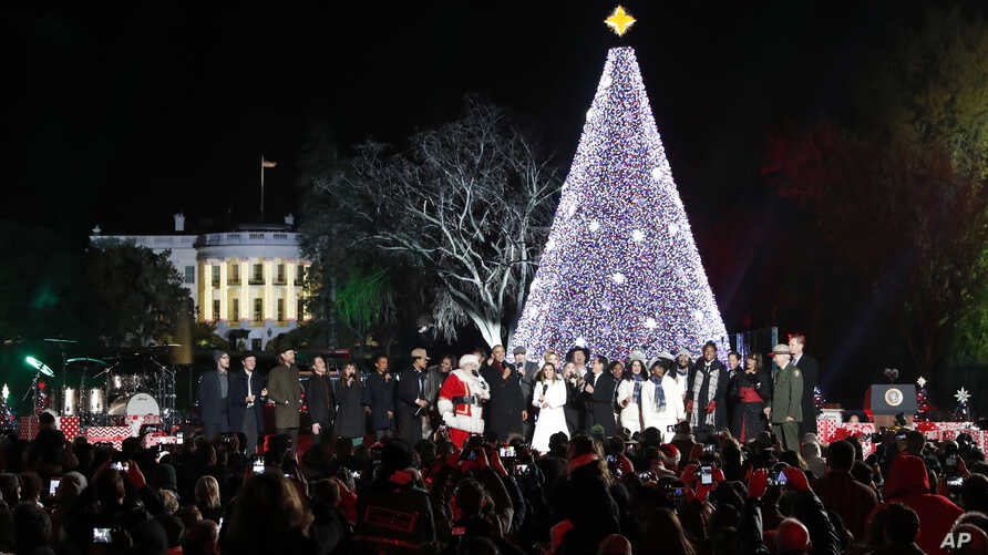 President Barack Obama, with Michelle Obama, and daughter Sasha, sing with Santa Claus and others during the lighting ceremony for the 2016 National Christmas Tree on the Ellipse near the White House, Dec. 1, 2016.