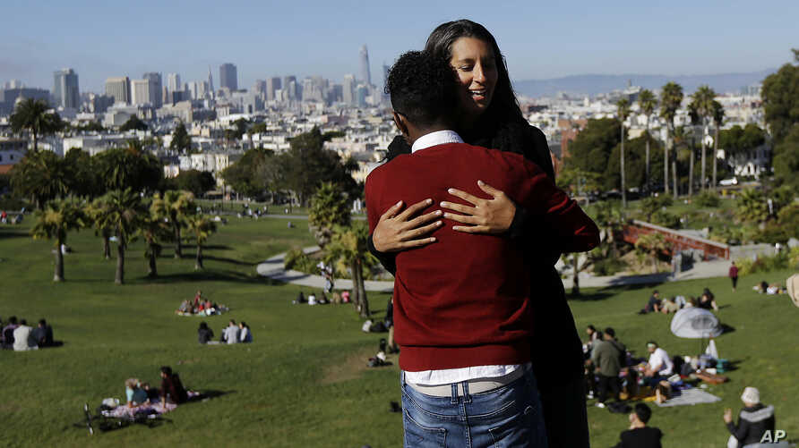 Julie Rajagopal, facing, hugs her 16-year-old foster child from Eritrea after posing for photos at Dolores Park in San Francisco, July 14, 2017. When he landed in March, he was among the last refugee foster children to make it into the U.S. Trump adm