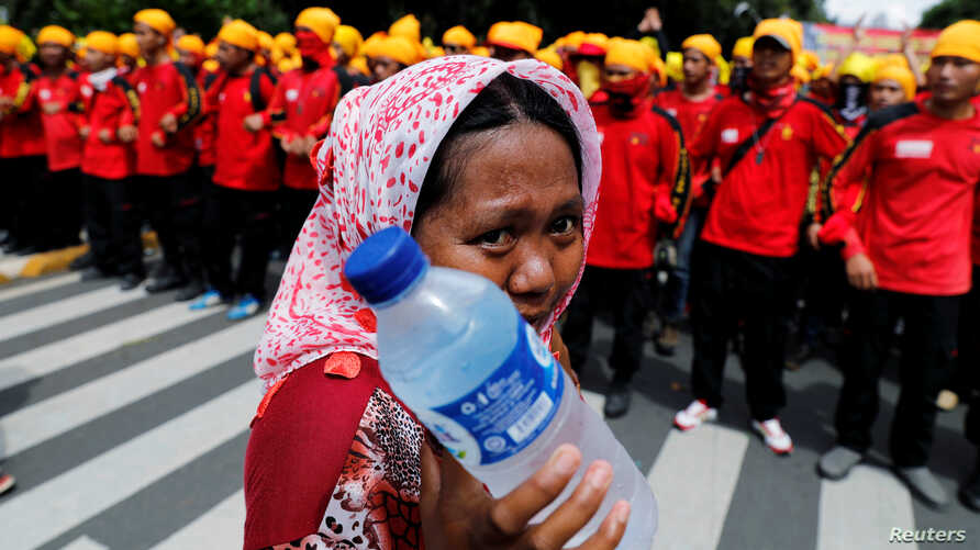 A street vendor holds drinking water as she walks near workers attending a May Day rally in front of presidential palace in Jakarta, Indonesia, May 1, 2016.
