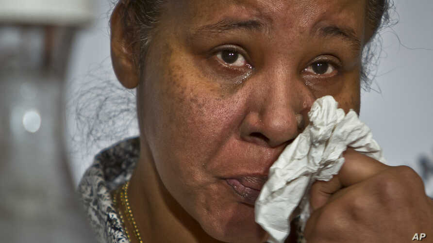 FILE - Esaw Snipes, the wife of police victim Eric Garner, wipes away tears as she speaks during a panel on police brutality at the 16th National Action Network's annual national convention opening, Wednesday, April 8, 2015.