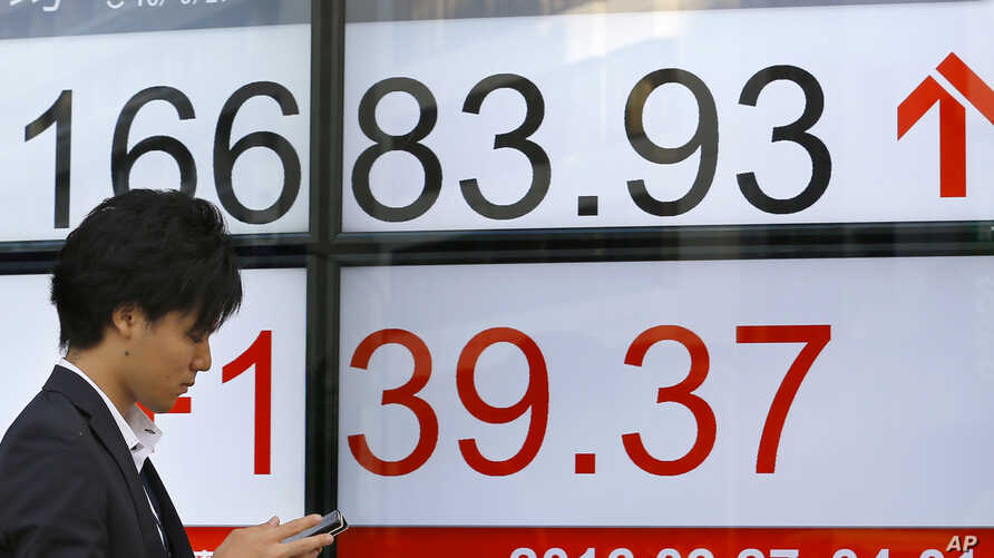 A man uses a mobile phone in front of an electronic stock indicator of a securities firm in Tokyo, Sept. 27, 2016.