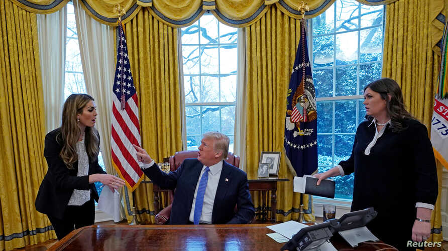 U.S. President Donald Trump confers with White House Communications Director Hope Hicks (L) as White House Press Secretary Sarah Sanders (R) listens during an interview with Reuters at the White House in Washington, U.S., January 17, 2018.