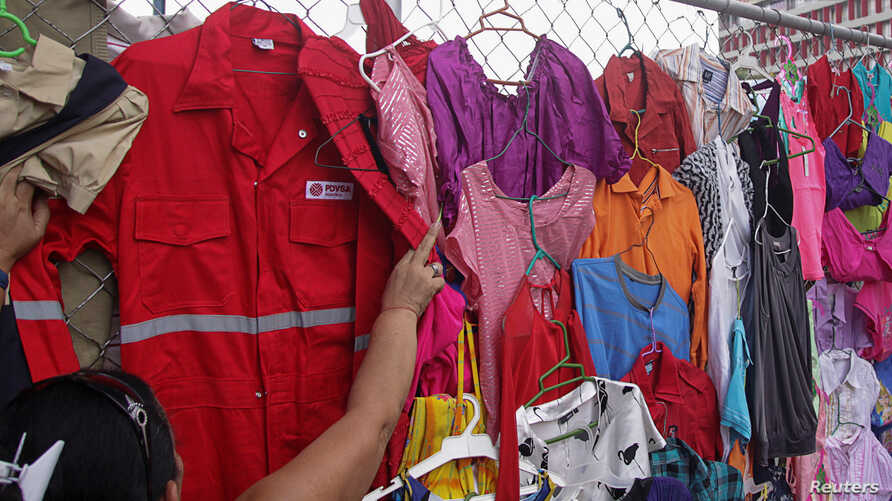 FILE -- A customer looks at PDVSA overalls for sale at a market in Maracaibo, Venezuela, September 11, 2016.