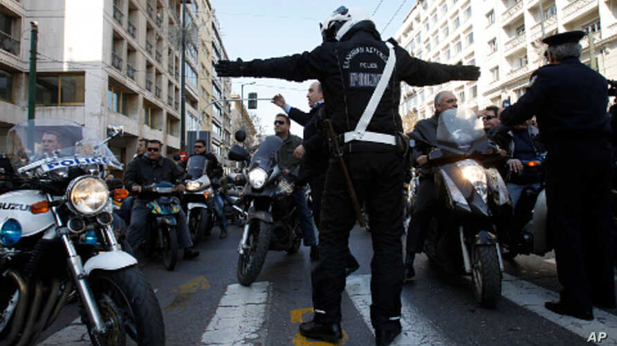 A traffic policeman tries to stop public transport employees as they ride on motorcycles during a protest in Athens, Feb 11, 2011