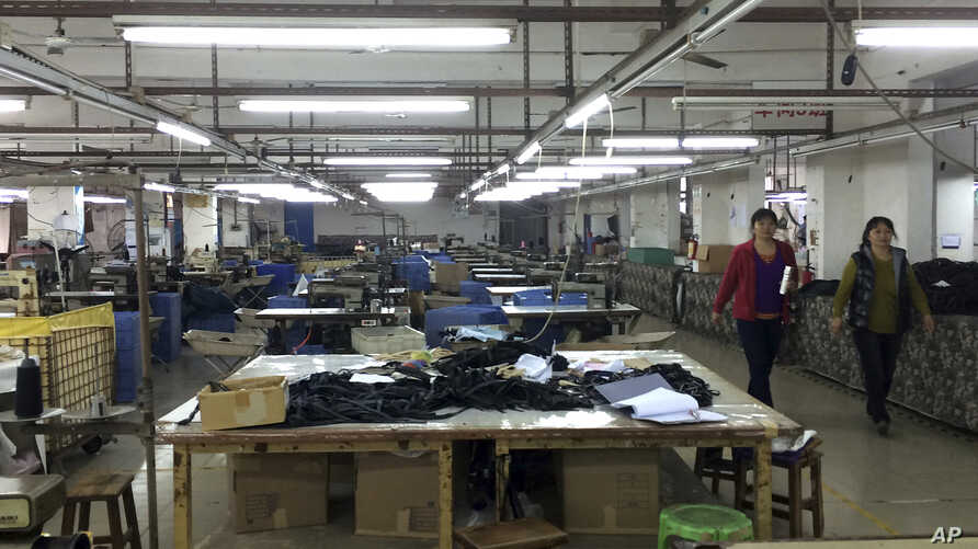 FILE - Workers walk past idle machinery as they strike at the Cuiheng Handbag Factory in Nanlang township in Zhongshan city in southern China's Guangdong Province, March 26, 2015.
