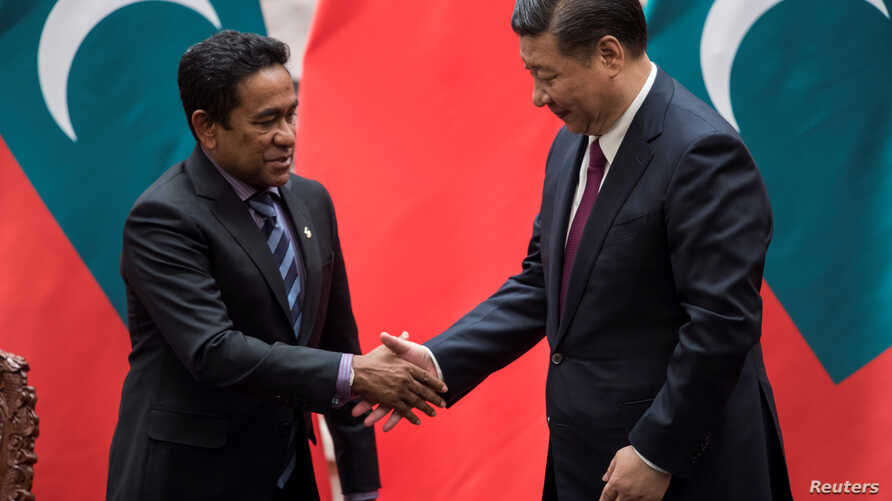 Maldives President Abdulla Yameen shakes the hand of China's President Xi Jinping after a signing meeting at the Great Hall of the People in Beijing, China, Dec. 7, 2017.