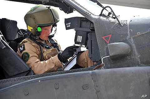 This is an undated handout photo issued by Britain's Ministry of Defense of Prince Harry as he prepares his Apache helicopter to go out on a mission in El Centro, California, February 8, 2012.