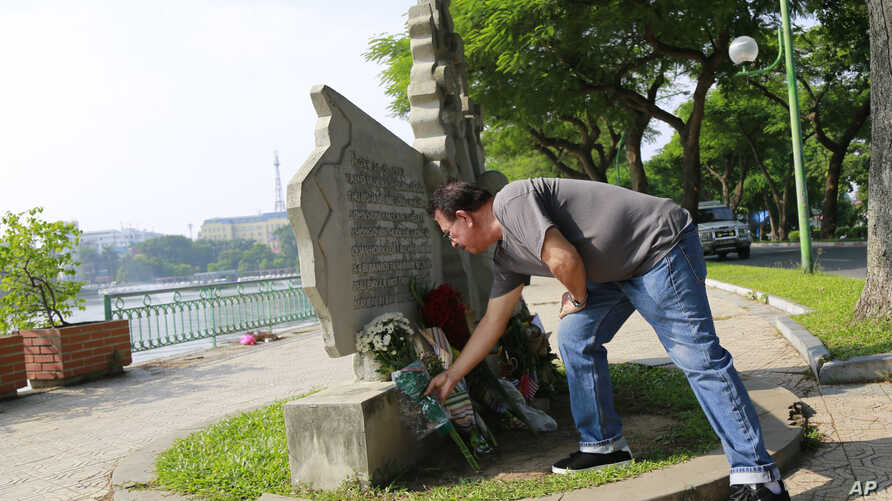 Victor Ramos, a Mexican man who has been living California for the past 35 years, lays flowers at the monument of U.S. Senator John McCain in Hanoi, Vietnam, Aug. 27, 2018.