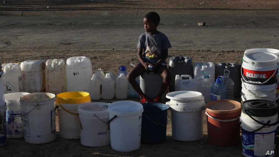 A boy keeps a spot in a queue for free water being transported in by the municipality, in Senekal, South Africa, Jan. 7, 2016.
