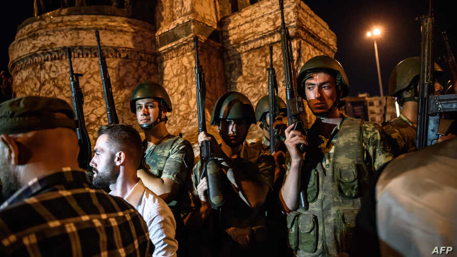 Turkish solders stay with weapons at Taksim Square as people protest against the military coup in Istanbul, July 16, 2016.