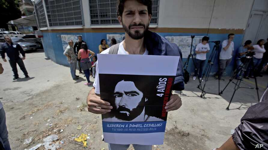 David Sosa, who was held at the political police SEBIN headquarters along with ex-mayor Daniel Ceballos and American citizen Joshua Holt, holds a poster of Ceballos outside the SEBIN headquarters and jail in Caracas, Venezuela, May 17, 2018.
