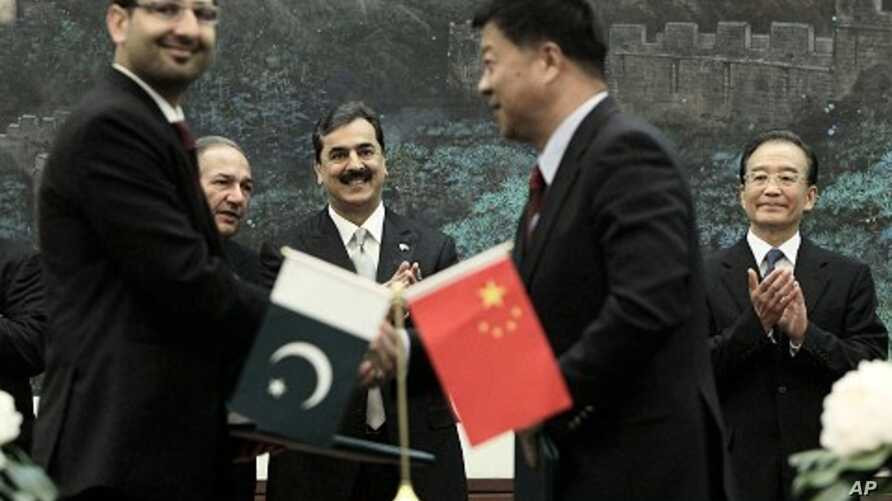 Pakistan's Prime Minister Yousuf Raza Gilani, center, and China's Premier Wen Jiabao, right, clap at a singing ceremony at the Great Hall of the People in Beijing, May 18, 2011