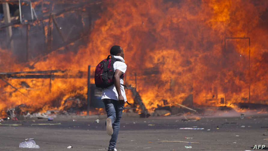 Zimbabwe's opposition supporters set up a burning barricade as they clash with police during a protest for electoral reforms, Aug. 26, 2016 in Harare, Zimbabwe.