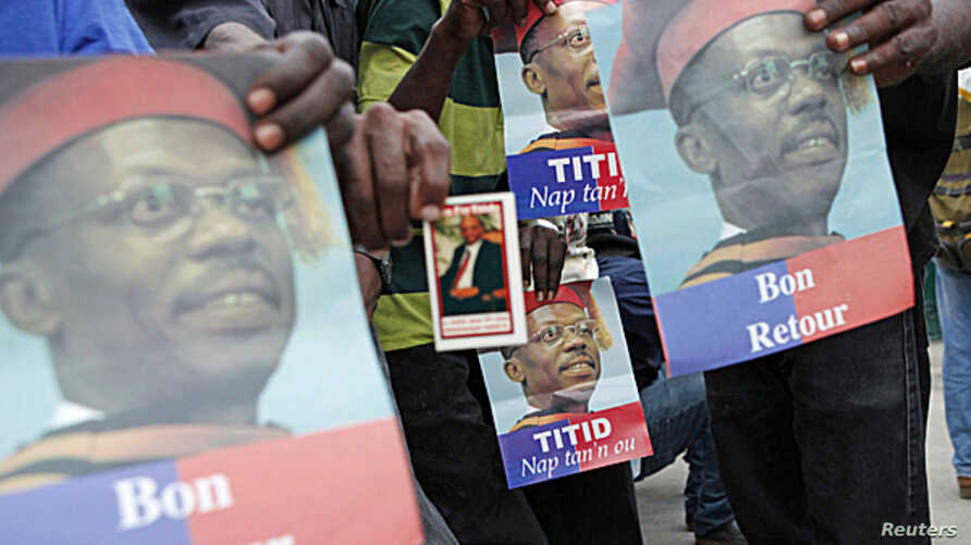Supporters of former Haitian President Jean-Bertrand Aristide wait outside his house for him to appear on his way to a court appearance, in the Tabarre neighborhood of Port-au-Prince, May 8, 2013.