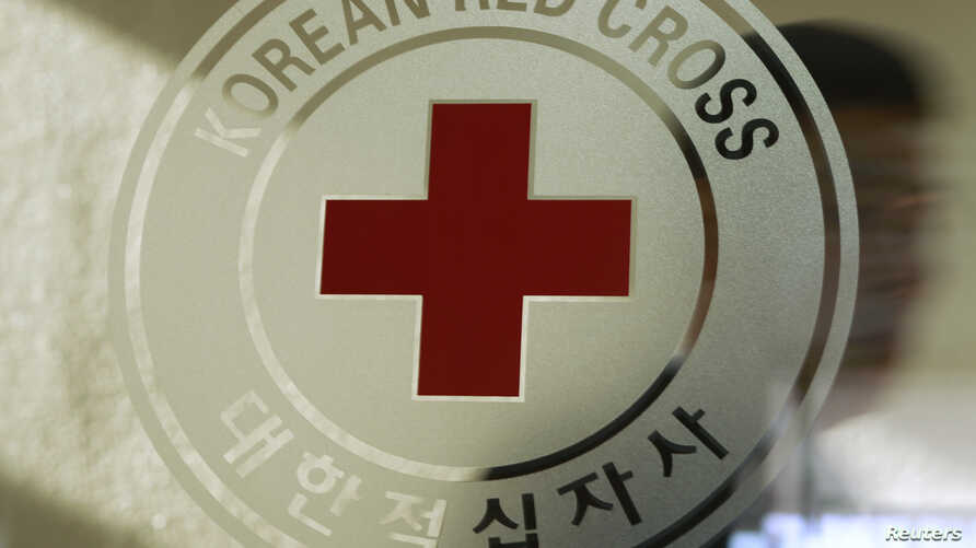 FILE - A man walks past a logo of the South Korean Red Cross at its headquarters in Seoul, Feb. 9, 2011. The International Federation of Red Cross emergency response teams, armed with water pumps, are helping irrigate fields hard hit by North Korea's