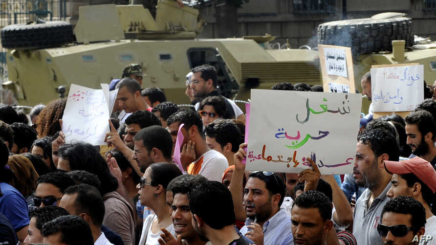 Unemployed Tunisian graduates hold signs as they shout slogans during a demonstration in Tunis to demand jobs and call for the resignation of the ruling government, September 29, 2012.