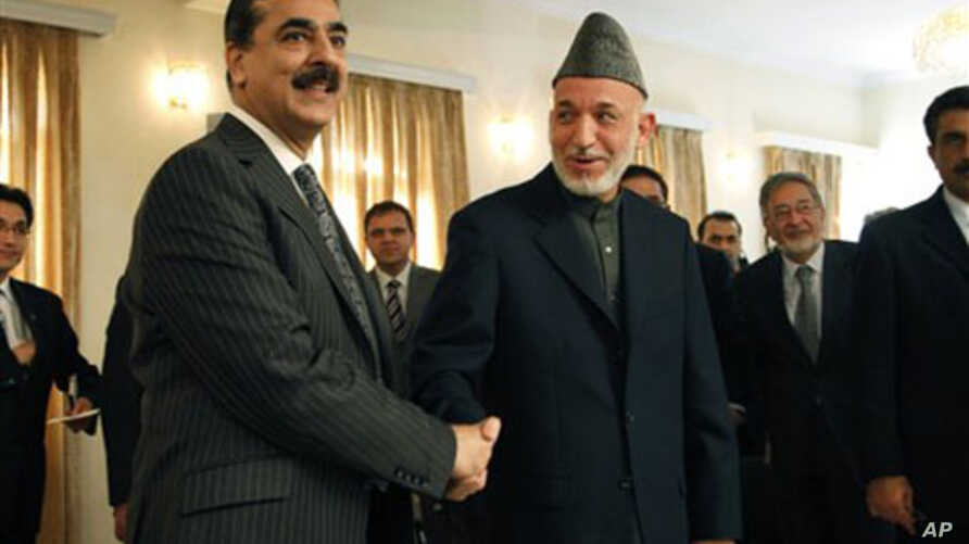 Afghan President Hamid Karzai, right, shakes hand with Pakistan's Prime Minister Yusuf Raza Gilani, after giving a joint press conference at the presidential palace in Kabul, Afghanistan, 04 Dec 2010