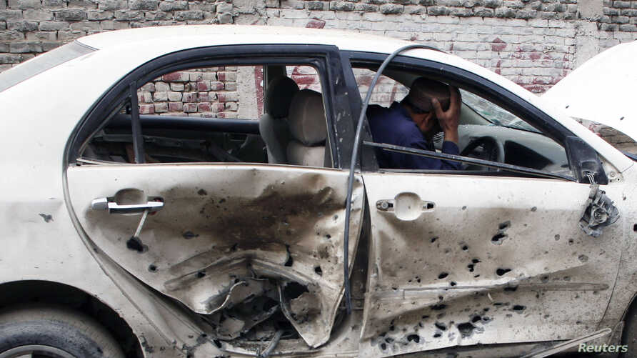 A man sits in his car which is damaged after a bomb attack in Quetta, April 24, 2013.