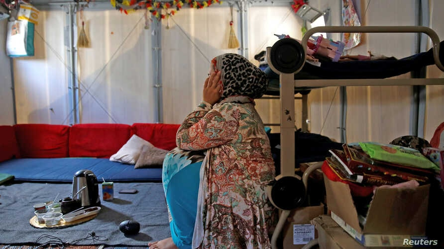 FILE - Syrian refugee Walaa, 26, sits inside her family's tent at the Souda municipality-run camp on the island of Chios, Greece, Sept. 7, 2016.