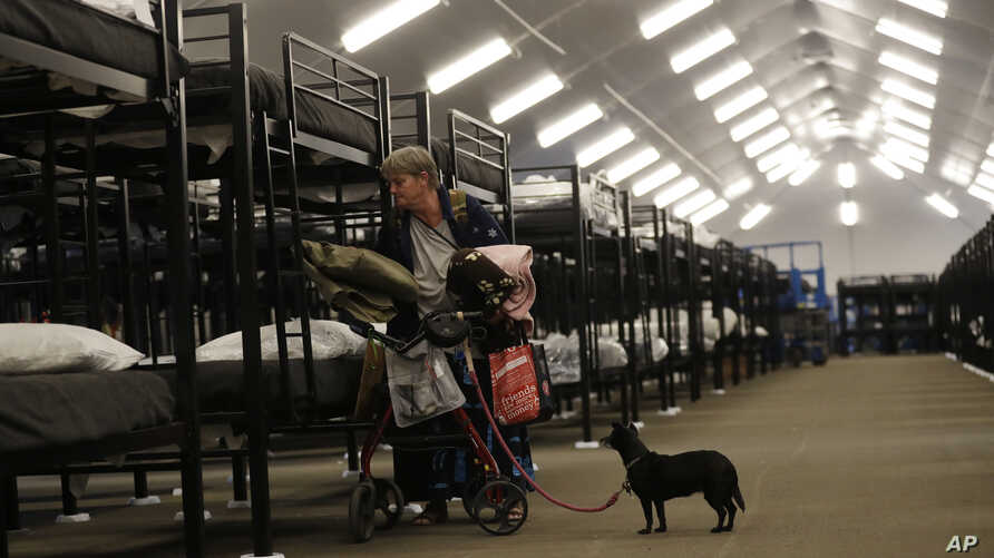 Verna Vasbinder prepares her new bunk in the city's new Temporary Bridge Shelter for the homeless as her dog, Lucy Lui, looks on, Dec. 1, 2017, in San Diego. The first of three shelters opened Friday, which will eventually provide beds for up to 700