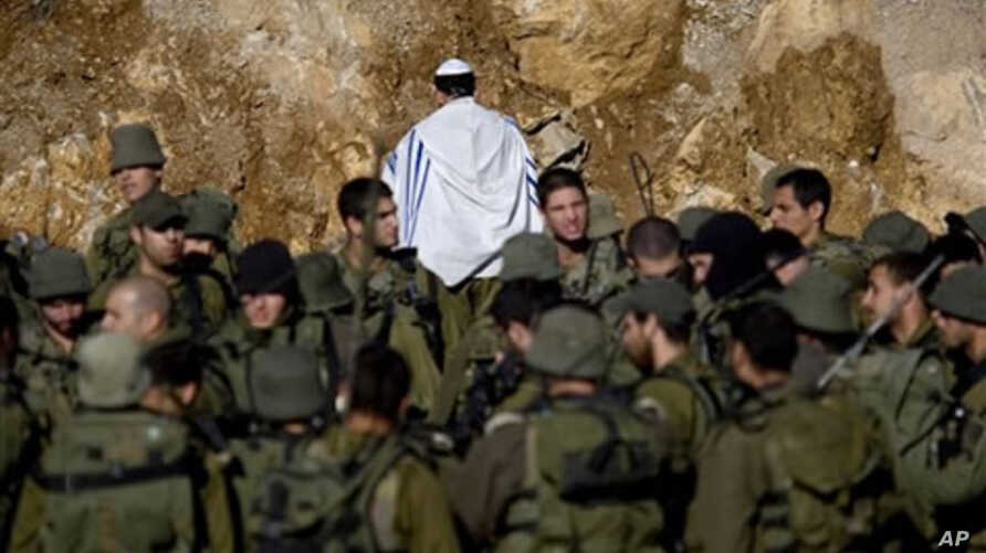 An Israeli soldier covered in a prayer shawl prays as Israeli troops gather near the border fence between Israel and Syria near the village of Majdal Shams in the Golan Heights,  May 16, 2011