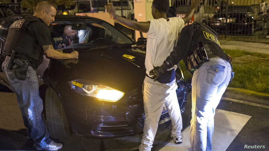 FILE - Cook County Sheriff police officers in Chicago, Illinois search a vehicle and a woman at street stop in the city's Austin neighborhood, September 9, 2015.