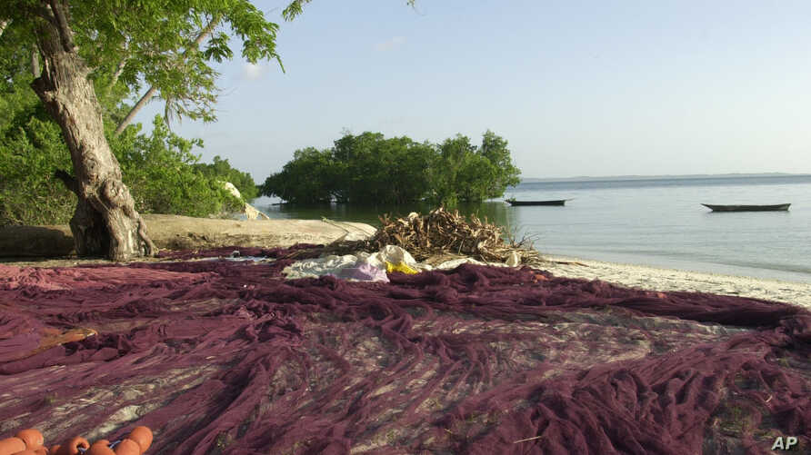 FILE - A fisherman's net is stretched out to dry on a beach on Pemba island, part of the Zanzibar archipelago 80 kilometers off the coast of Tanzania in the Indian Ocean. It's a perfect tropical island getaway.