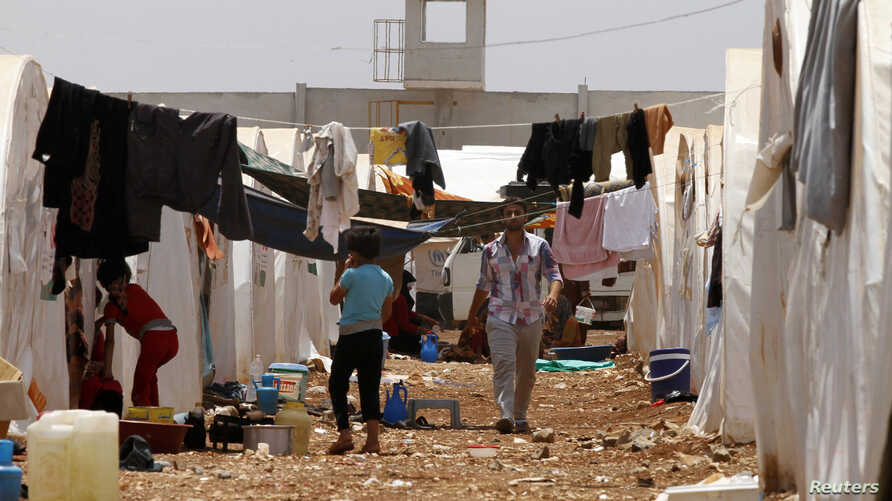 Syrian refugees walk under clothing lines at the Bab Al-Salam refugee camp in Azaz, near the Syrian-Turkish border June 9, 2013. REUTERS/Hamid Khatib (SYRIA - Tags: SOCIETY POLITICS CIVIL UNREST) - RTX10HM6