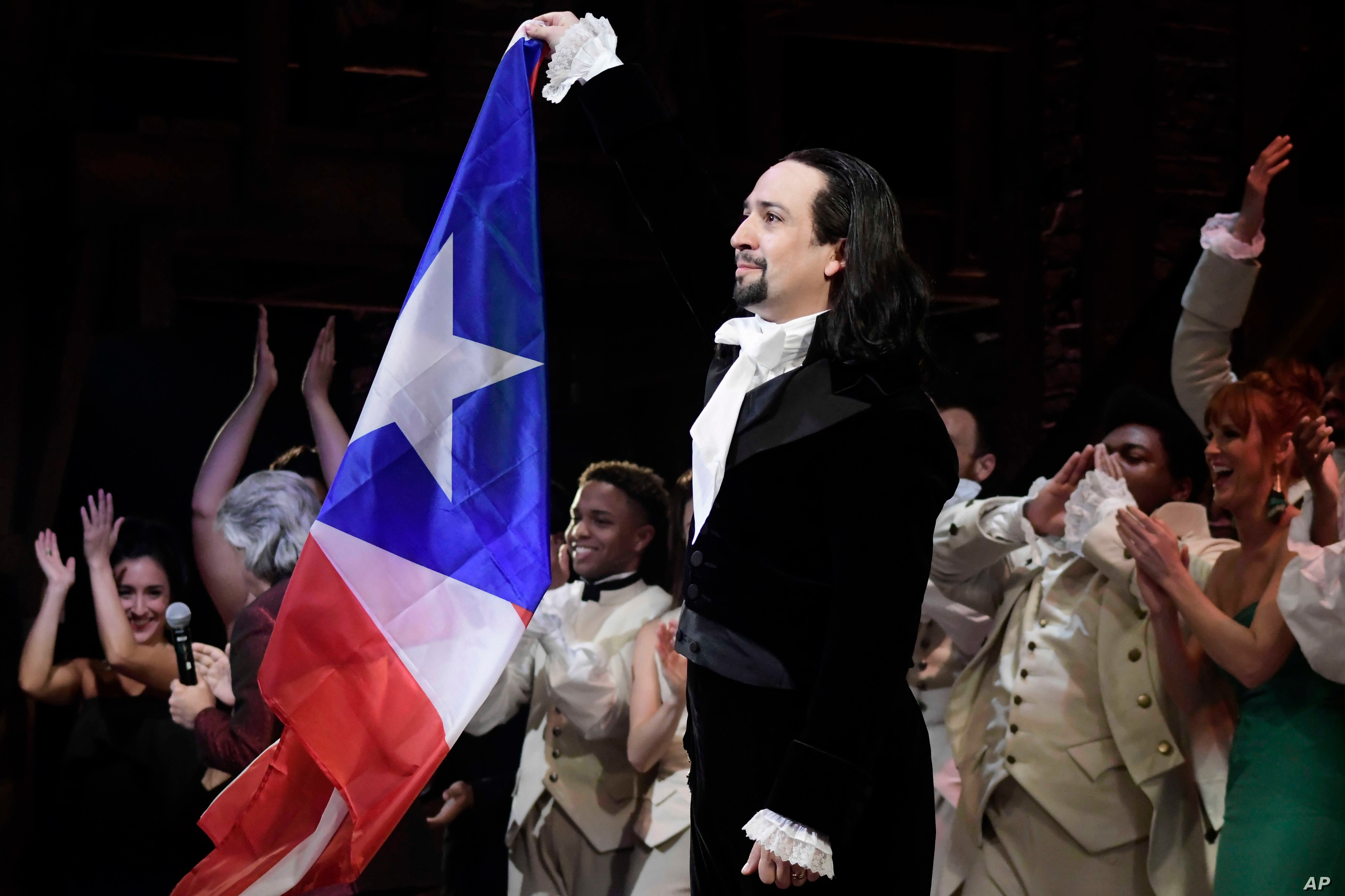 "Lin-Manuel Miranda, composer and creator of the award-winning Broadway musical, ""Hamilton,"" proudly waves a Puerto Rican flag after receiving a standing ovation at the premiere in San Juan, Puerto Rico, Jan. 11, 2019. The musical is to run for two w"