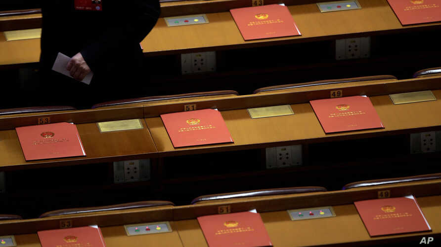 FILE - A delegate walks past copies of draft resolutions placed on delegates' desks of the annual National People's Congress in Beijing's Great Hall of the People, March 16, 2016.