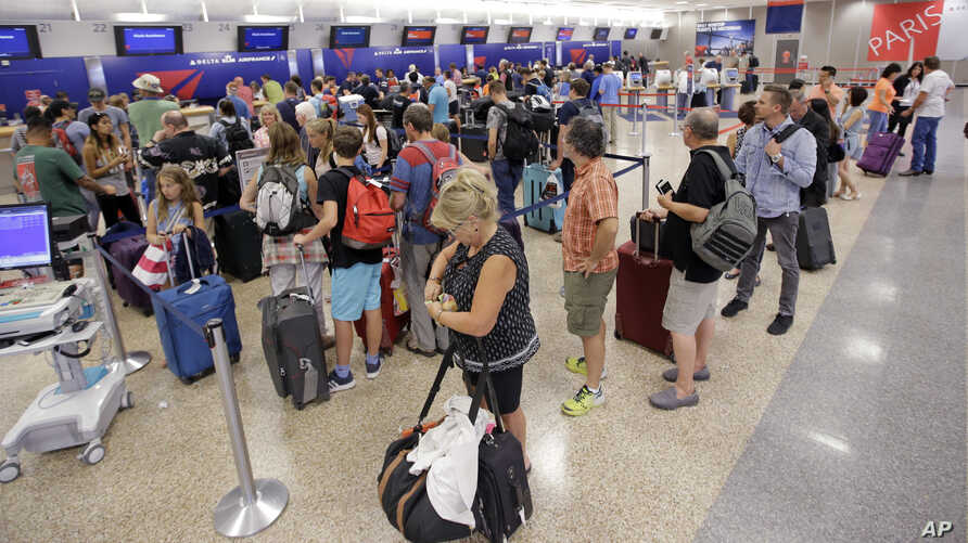 Delta Air Lines passengers stand in line after flights resumed Aug. 8, 2016, in Salt Lake City, following a computer outage.