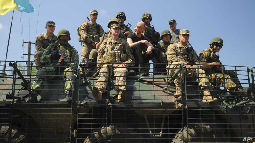 Ukraine's Prime Minister Arseniy Yatsenyuk, center, surrounded by U.S. and Ukrainian soldiers atop an armored personnel carrier in Lviv region, western Ukraine, June 3, 2015.