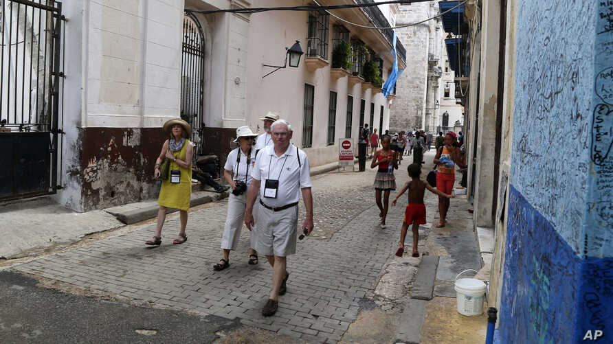 U.S. tourists walks outside the Bodeguita del Medio Bar frequented by the late American novelist Ernest Hemingway in Old Havana, Cuba, May 24, 2015. One airline's cutback in flights to Cuba may be a sign that demand for travel to the island is slowin
