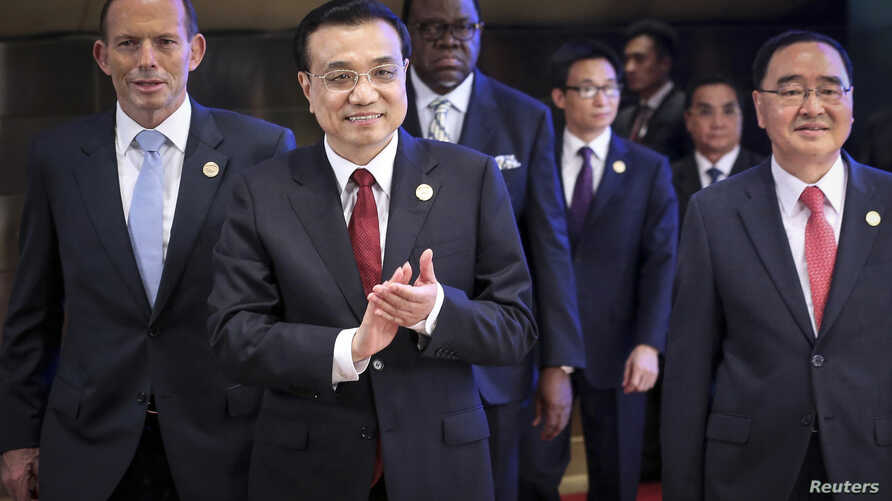 Chinese Premier Li Keqiang (2nd L) claps as he walks with Australian Prime Minister Tony Abbott (L), South Korean Prime Minister Jung Hong-won (R) during the opening ceremony of the Boao Forum for Asia (BFA) Annual Conference 2014 in Boao, Hainan pro