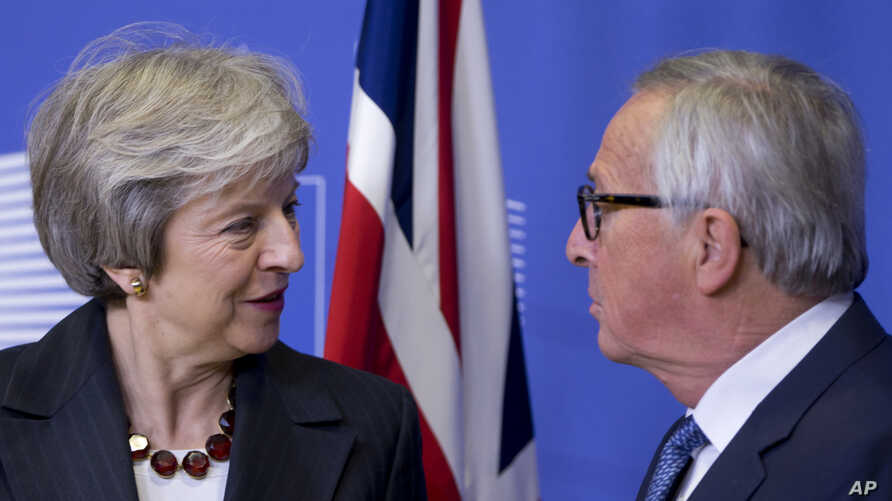 European Commission President Jean-Claude Juncker, right, greets British Prime Minister Theresa May at EU headquarters in Brussels, Wednesday, Nov. 21, 2018. British Prime Minister Theresa May meets with European Commission President Jean-Claude Junc