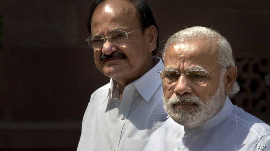 Indian PM Narendra Modi, right, talks to media upon his arrival at the parliament house as Venkaiah Naidu stands along in New Delhi, India, April 25, 2016.