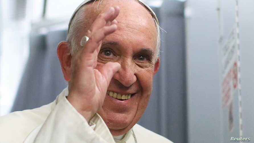 Pope Francis smiles onboard the papal plane during his return to Rome, from Asuncion, Paraguay, July 13, 2015.