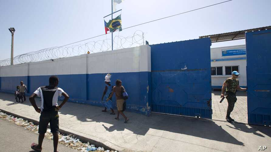 FILE -  a Brazilian U.N. peacekeeper opens a gate at the U.N. base in the Cite Soleil slum of Port-au-Prince, Haiti.