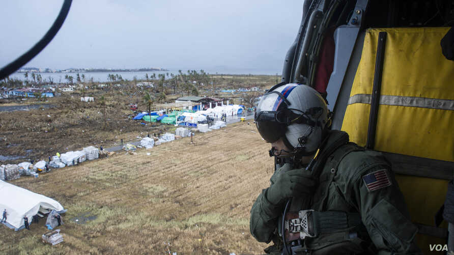 A U.S Navy aircrewman prepares to drop supplies from a MH-60S Seahawk, assigned to the USS George Washington at Tacloban Air Base in support of Operation Damayan, Nov. 14, 2013. (U.S. Navy photo/Ricardo R. Guzman)