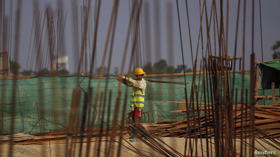 FILE - A man works at the site of the Thilawa Special Economic Zone (SEZ) project at Thilawa, Myanmar, May 8, 2015.