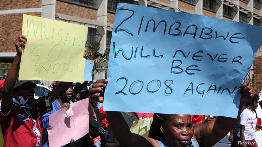 Zimbabweans hold placards during a protest against President Robert Mugabe government's handling of the economy in Harare, Zimbabwe, August 3, 2016.