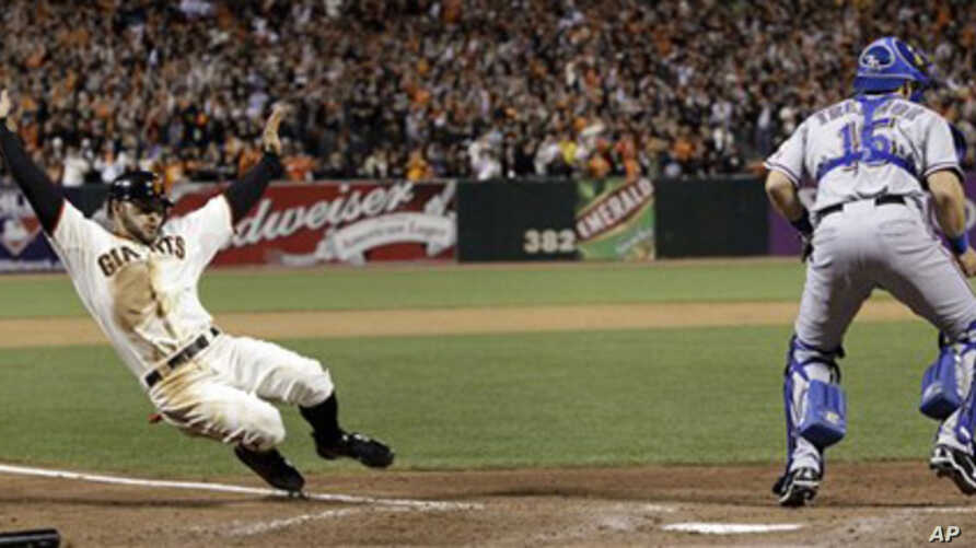 San Francisco Giants' Cody Ross slides safely home in front of Texas Rangers' Matt Treanor during the seventh inning of Game 2 of baseball's World Series Thursday, Oct. 28, 2010, in San Francisco.