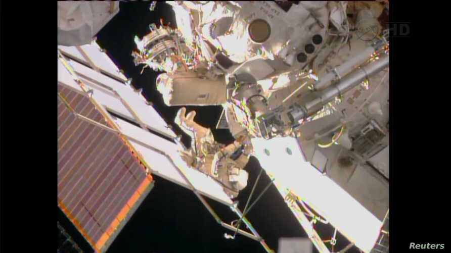 FILE - Two Russian cosmonauts are seen working outside the International Space Station during a spacewalk in this still image taken from NASA handout video.