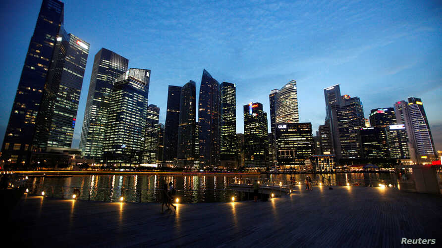FILE - People walk past the skyline of Marina Bay central business district in Singapore, Apr. 26, 2013.