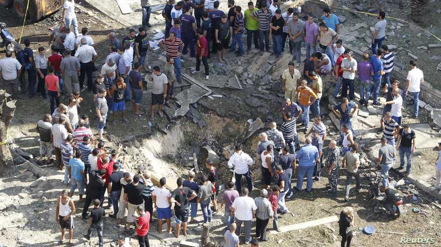 Residents gather around a crater caused by one of the two explosions outside one of two mosques in Lebanon's northern city of Tripoli, August 23, 2013.