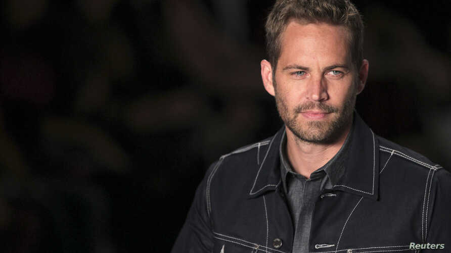 U.S. actor Paul Walker presents a creation from Colcci's 2013/2014 summer collection during Sao Paulo Fashion Week, March 21,2013.