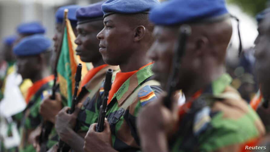 Ivory Coast soldiers stand at guard during a ceremony to honor soldiers killed in last month's al-Qaida attack on the beach resort town of Grand Bassam, in Abidjan, April 8, 2016.