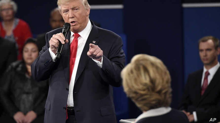 Republican presidential nominee Donald Trump points at Democratic presidential nominee Hillary Clinton as he speaks during the second presidential debate at Washington University in St. Louis, Oct. 9, 2016.