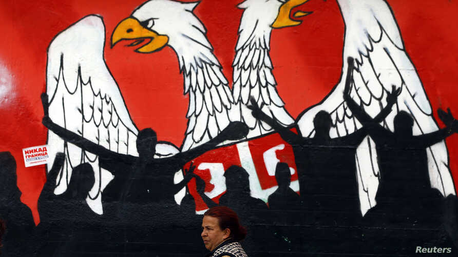 A woman walks past a graffiti depicting part of the Serbian coat of arms in the northern Serb dominated, part of the ethnically divided town of Mitrovica, Kosovo, April 3, 2013.